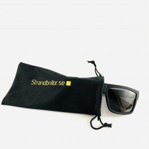 Svarta solglasögon med bred båge och skyddande påse