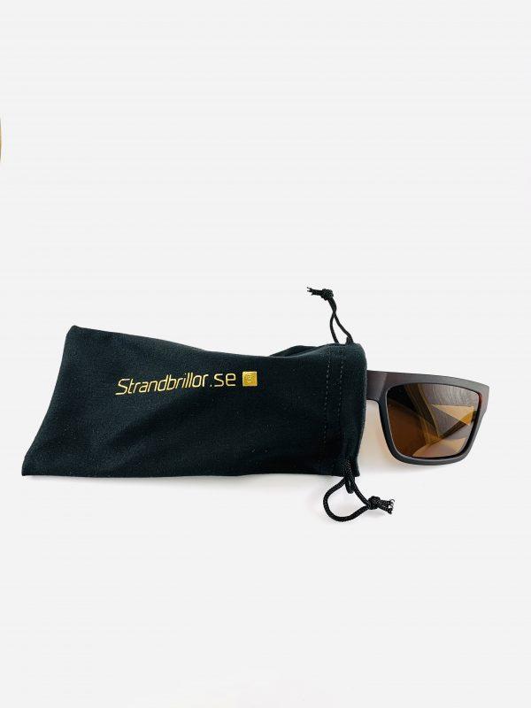Svarta solglasögon med bred båge och brunt glas i skyddande påse