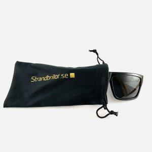 Svarta solglasögon med bred båge och svart glas i skyddande påse