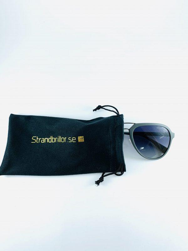 Solglasögon i mörkt glas med stiliga pilotbågar i grått och tillhörande förvaring