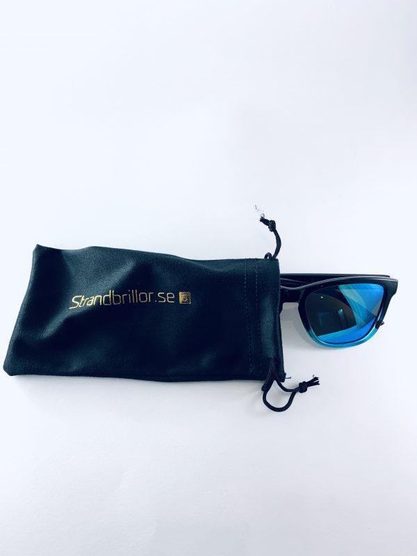 Deeros Solglasögon med blanksvarta bågar och blått glas med förvaringspåse