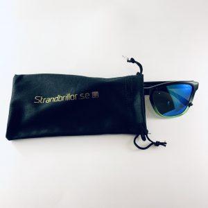 Solbrillor med gröna inslag och dess förvaringspåse
